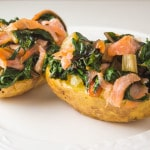 two potato halves loaded with smoked salmon and swiss chard