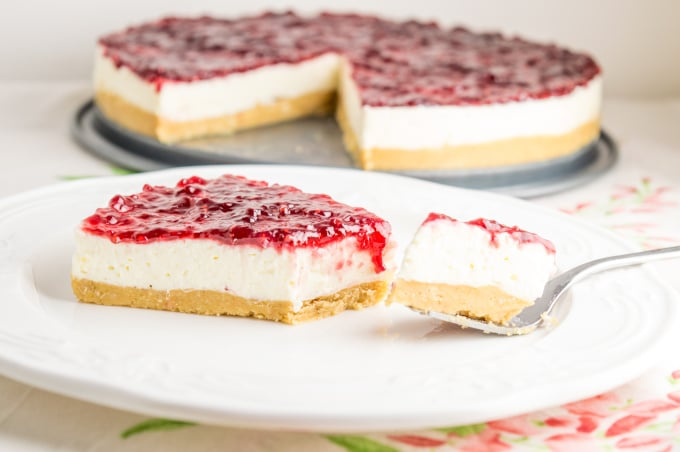 a slice of raspberry cheesecake cut with a fork, with the rest of the cake on the background.