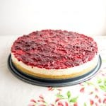 A cheesecake covered with raspberry jam, on a flower tablecloth