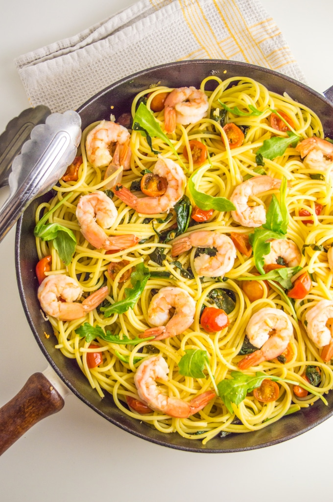 A skillet with shrimp, tomatoes and spinach pasta topped with arugula
