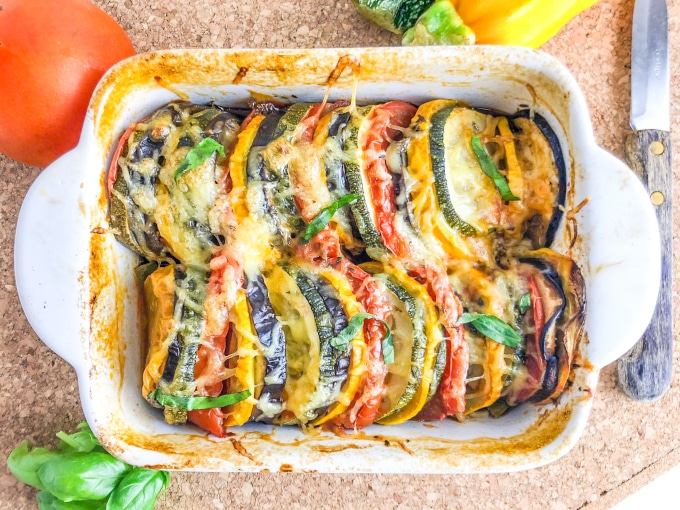Close-up of an oven dish with colorful baked vegetable slices, topped with cheese
