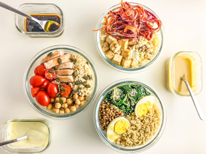 three round nourish bowls with three dressings in a rectangular container