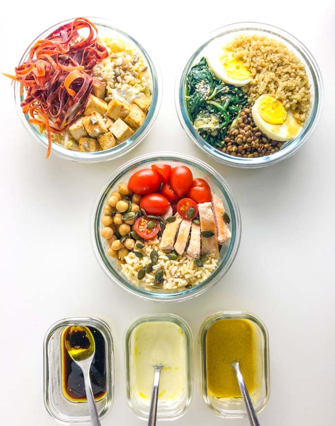 three packed nourish bowls with three dressings in a rectangular container