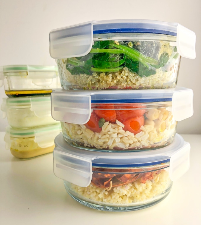 three filled lunchboxes and three dressing containers, both stacked