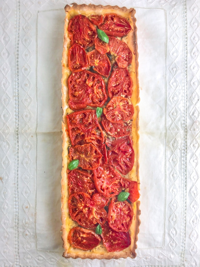 A rectangular shaped tart filled with tomatoes and garnished with basil leaves