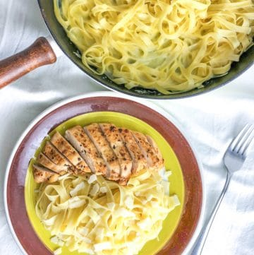 A plate with fettuccine alfredo with chicken and a skilled with pasta