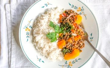 a plate with half rice, half lentils with vegetables