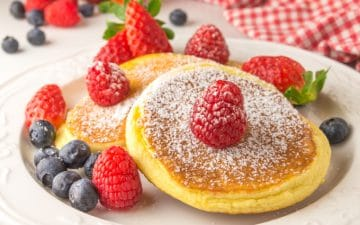 closeup of a plate with a fluffy pancake topped with raspberries