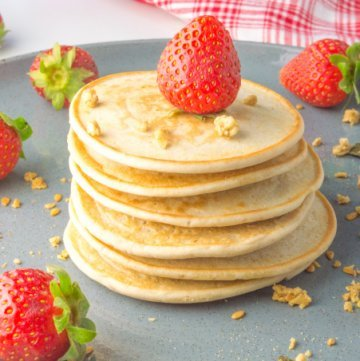 pile of pancakes with strawberries on a plate