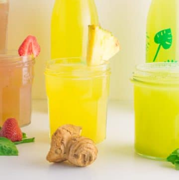 three glasses with pink, yellow and green agua fresca and decorated with fruits and leaves