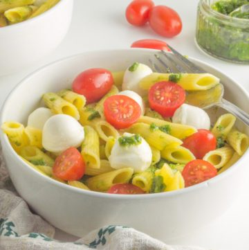 bowl filled with caprese pasta salad with pesto