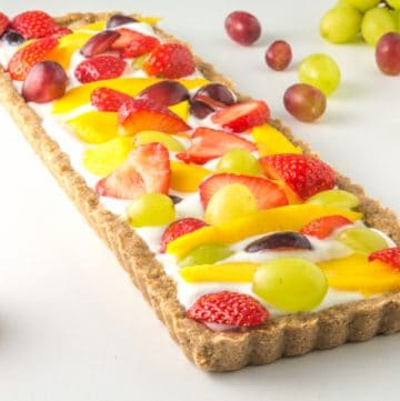 a low fodmap fruit tart surrounded by fresh fruit
